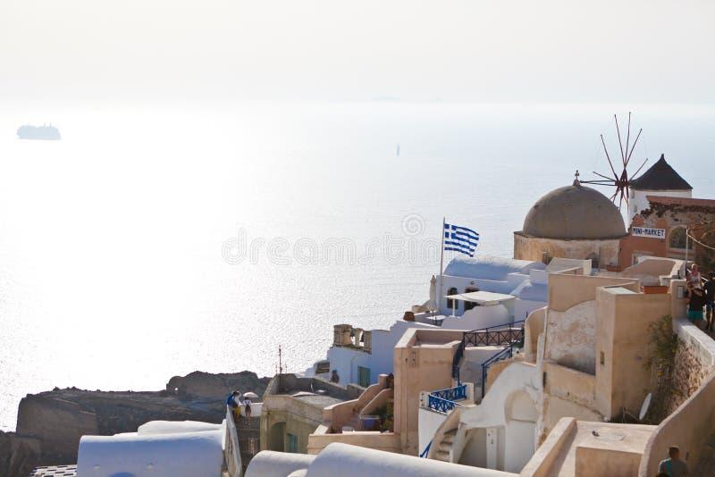 Sikt av traditionella vita hus och kyrkor med blåa kupoler över calderaen i den Oia staden på den Santorini ön royaltyfri foto