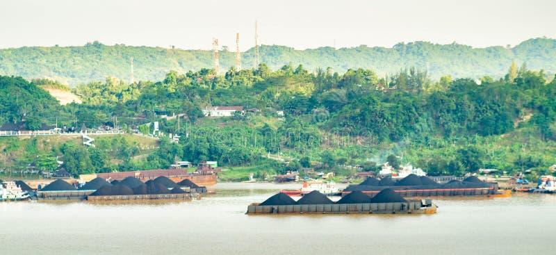 Sikt av trafik av bogserbåtar som drar pråm av kol på den Mahakam floden, Samarinda, Indonesien arkivfoto