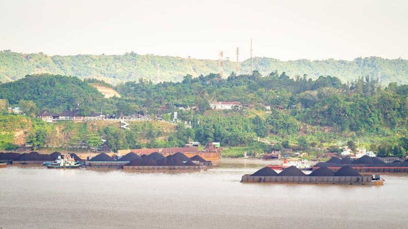 Sikt av trafik av bogserbåtar som drar pråm av kol på den Mahakam floden, Samarinda, Indonesien arkivfoton