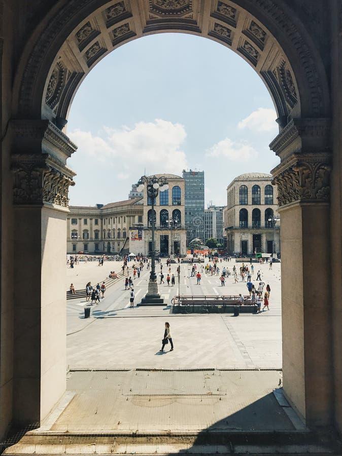 Sikt av turister som går på Piazza del Duomo till och med arkivbågen royaltyfria bilder