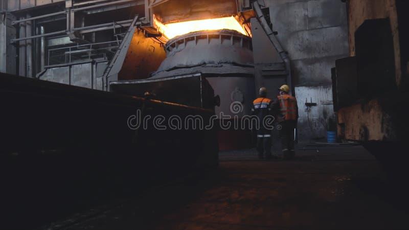 Sikt av två arbetare från baksida i likformig och hjälmar på bakgrund av den mörka smutsiga fabriken footage Två anställda överva arkivfoton