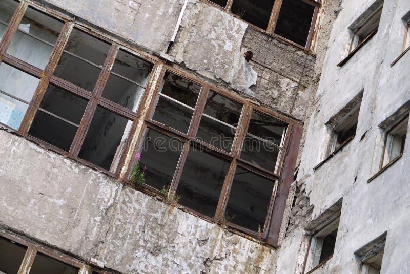 Sikt av väggarna och de tomma fönstren av en övergiven byggnad royaltyfri fotografi