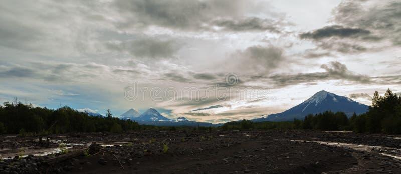 Sikt av volcanoes: Ostry Tolbachik, Klyuchevskaya Sopka, Bezymianny, Kamen från floden Studenaya på gryning kamchatka arkivfoto