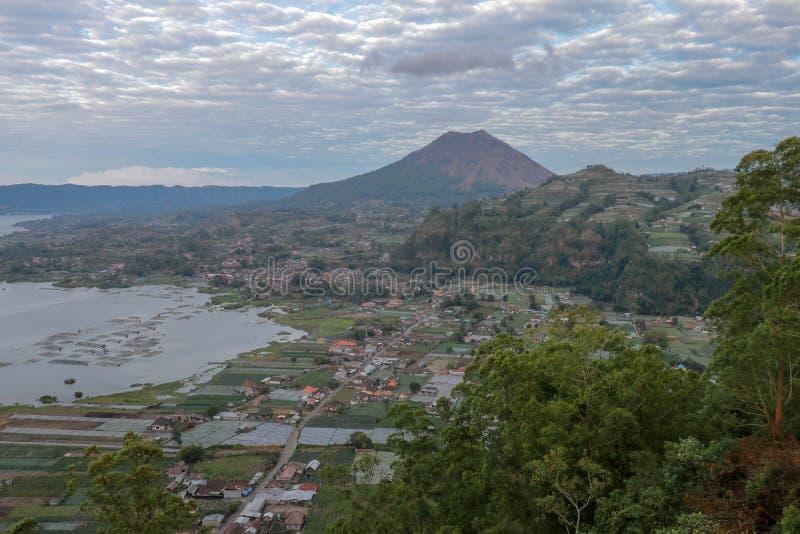 Sikt bak den Batur vulkan på caldera med sjön och det motsatta Abang berget Sjö med termiska vårar 80 bacteriesdagar g?r varje f? arkivfoton