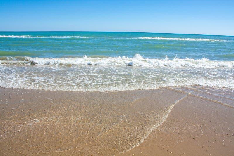Sikt för Adriatiskt havkust Kust av Italien, sandig strand för sommar med moln på horisont fotografering för bildbyråer
