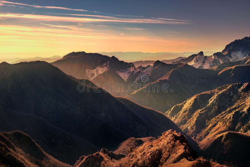 Sikt för Alpi Apuane berg- och marmorvillebråd på solnedgången Carrara arkivfoto