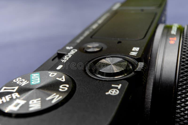 Sikt för bästa sida av en svart kompakt kamera, sneglande till baksidan, med lågt djup av fältet fotografering för bildbyråer