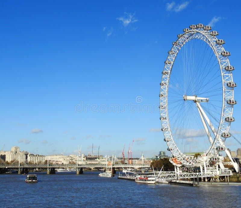 Sikt för blå himmel av den södra banken för London ` s och det London ögat från den Westminster bron arkivfoto