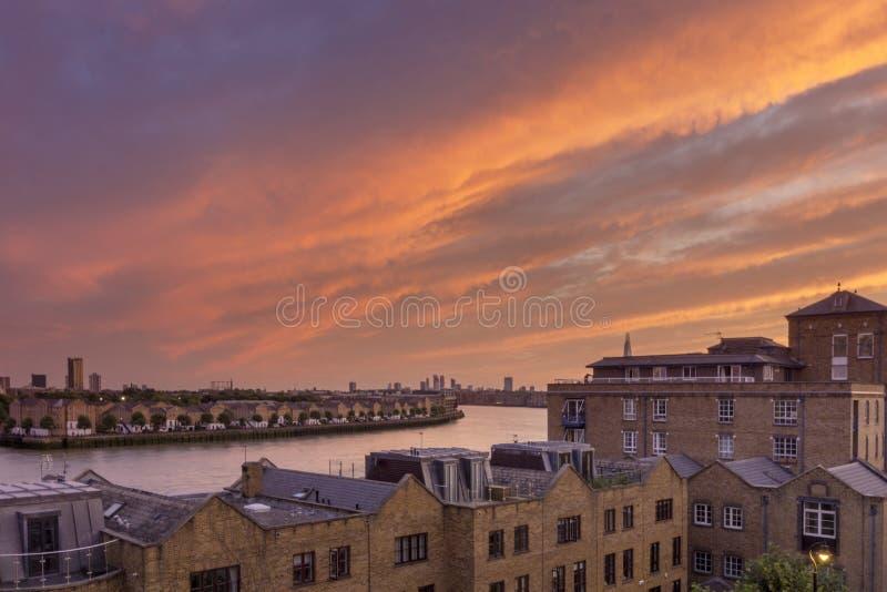 Sikt för cloudscape för solnedgång för kanariefågelhamnplatsflodstrand, London stad arkivfoto