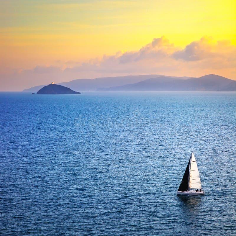 Sikt för Elba ösolnedgång från Piombino ett seglafartyg Mediterranea royaltyfria bilder