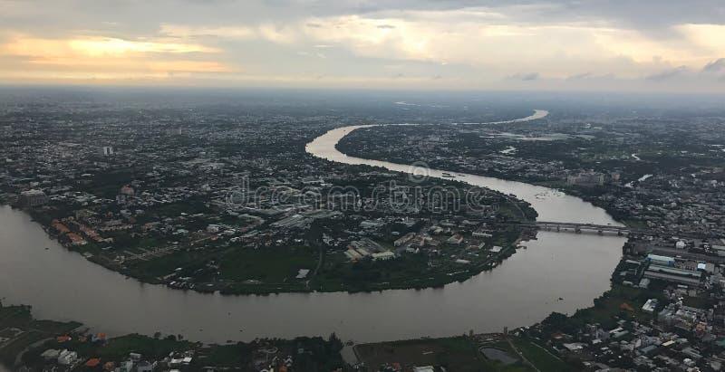 Sikt för fågelöga från plant fönster: Ho Chi Minh City med att slingra den Saigon floden på skymning på en regnig dag arkivbild