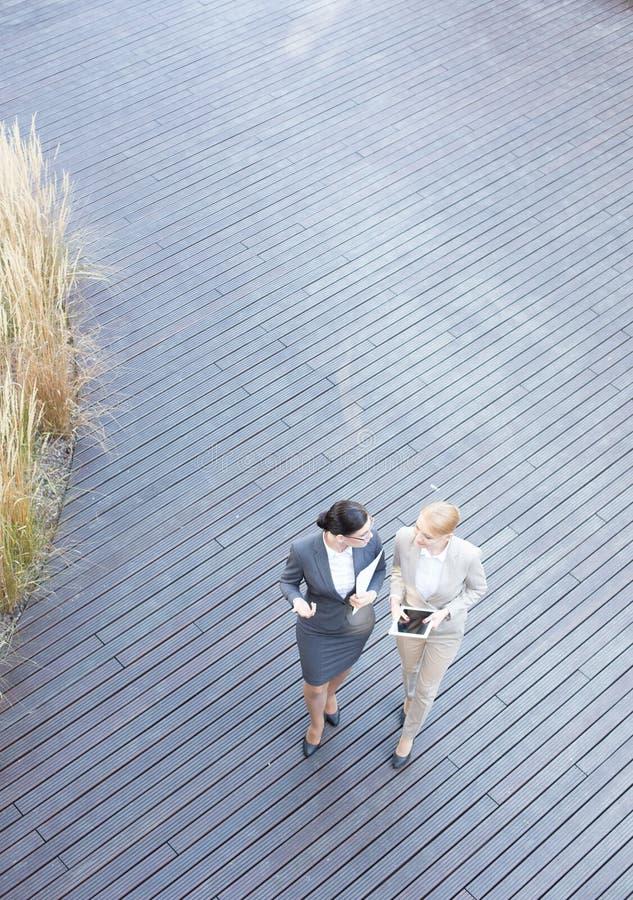 Sikt för hög vinkel av affärskvinnor som diskuterar, medan gå på golvtilja royaltyfria foton