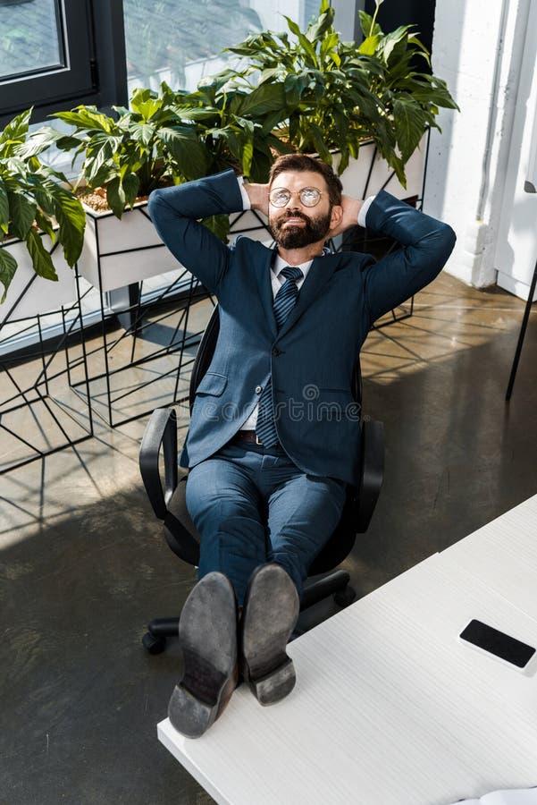 sikt för hög vinkel av att le den skäggiga affärsmannen som kopplar av med ben på tabellen och händer bak huvudet royaltyfri bild
