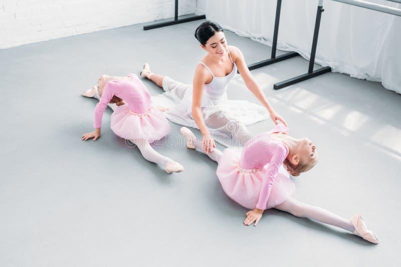 sikt för hög vinkel av att le den unga läraren med gulligt litet öva för ballerina royaltyfri bild