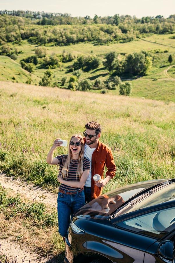 sikt för hög vinkel av att le stilfulla par i solglasögon med kaffekoppen som tar selfie på smartphonen nära bilen på lantligt arkivfoton