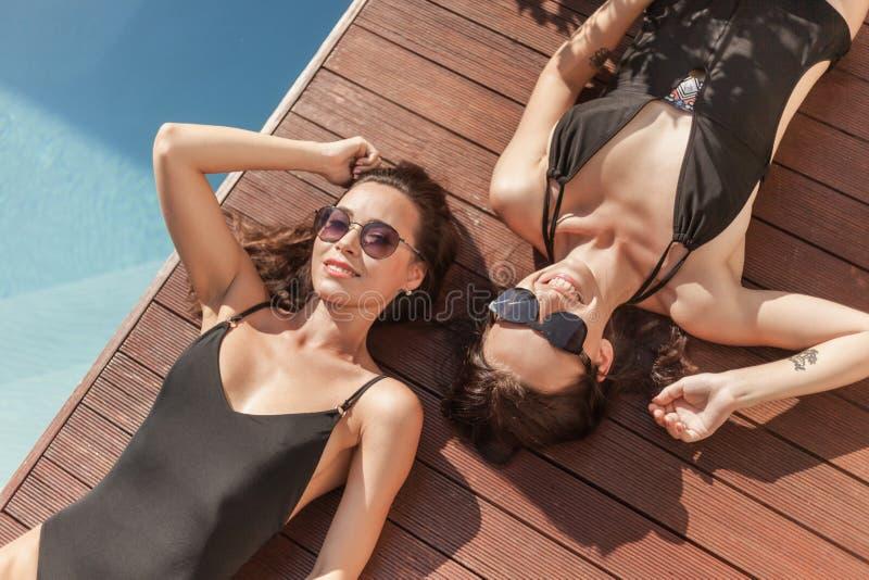 sikt för hög vinkel av attraktiva unga kvinnor, i att ligga för baddräkter arkivbild