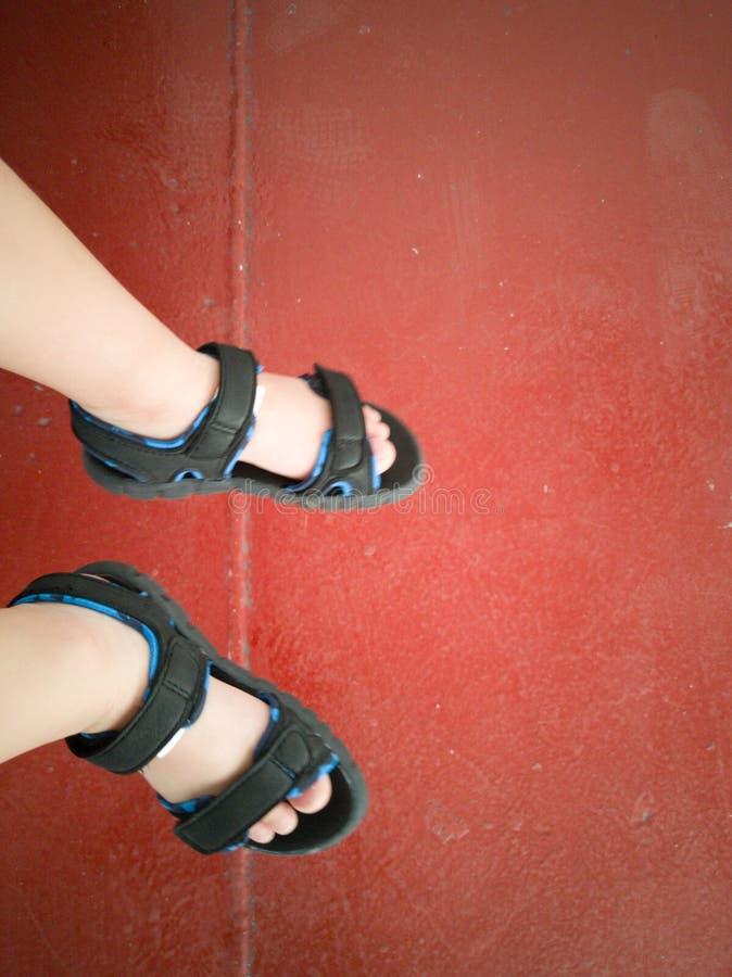 Sikt för hög vinkel av child& x27; s-fot med sandaler på rött golv fotografering för bildbyråer