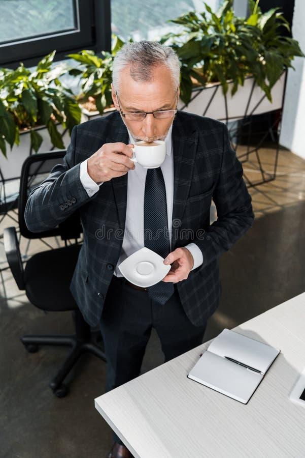sikt för hög vinkel av den mogna affärsmannen som dricker kaffe fotografering för bildbyråer