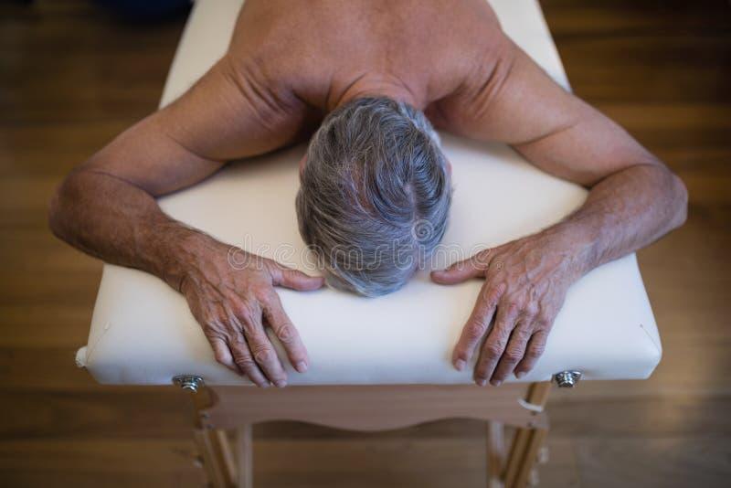 Sikt för hög vinkel av den shirtless höga manliga patienten som ligger på säng arkivbilder