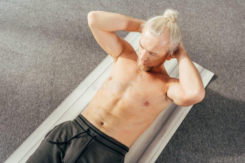 sikt för hög vinkel av den shirtless mannen som gör abs för att öva på matt yoga arkivbild