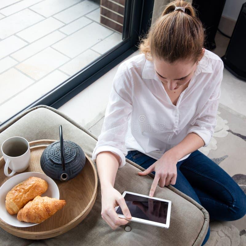 Sikt för hög vinkel av den unga kvinnan som använder minnestavlan på frukosten royaltyfri fotografi