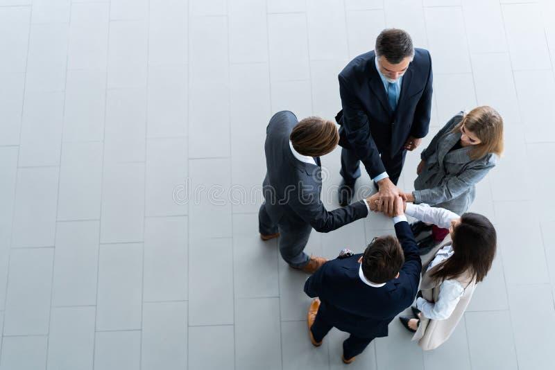 Sikt för hög vinkel av ett lag av eniga coworkers som tillsammans står med deras händer i ett bråte i det moderna kontoret royaltyfri fotografi