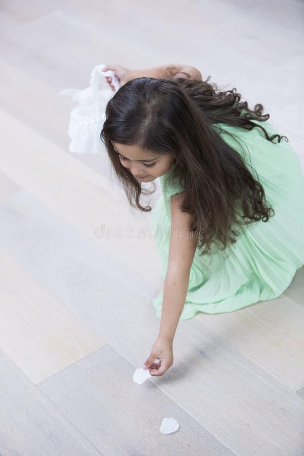 Sikt för hög vinkel av flickan som upp hemma väljer blommakronblad från golv arkivfoto