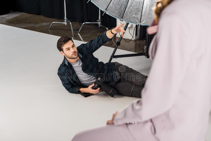 sikt för hög vinkel av fotografen med kameran som ligger och förklarar arbete till den kvinnliga modellen royaltyfri fotografi