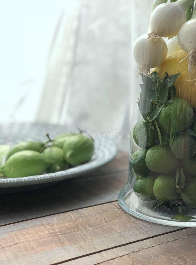 Sikt för hög vinkel av gröna tangerin, citroner och vårlökar i den glass vasen arkivfoton
