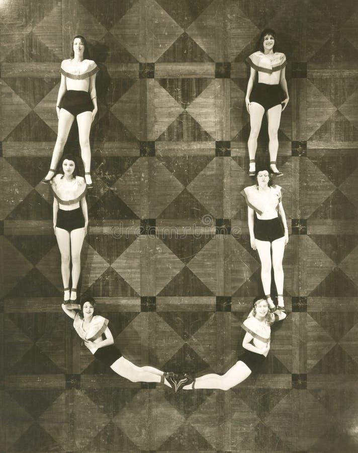 Sikt för hög vinkel av kvinnor som bildar bokstaven U royaltyfri illustrationer