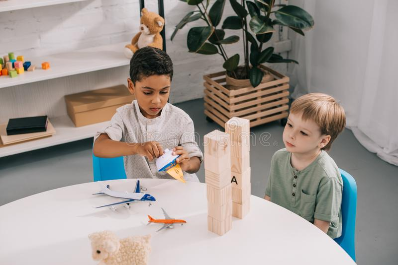 sikt för hög vinkel av mångkulturella pojkar som spelar med leksaker i klassrum royaltyfri bild