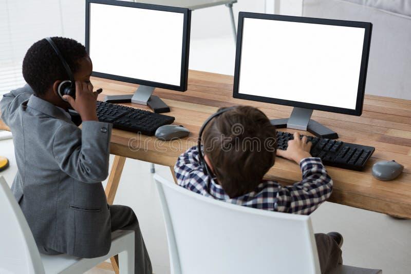Sikt för hög vinkel av manliga kollegor som talar till och med hörlurar med mikrofon på skrivbordet fotografering för bildbyråer