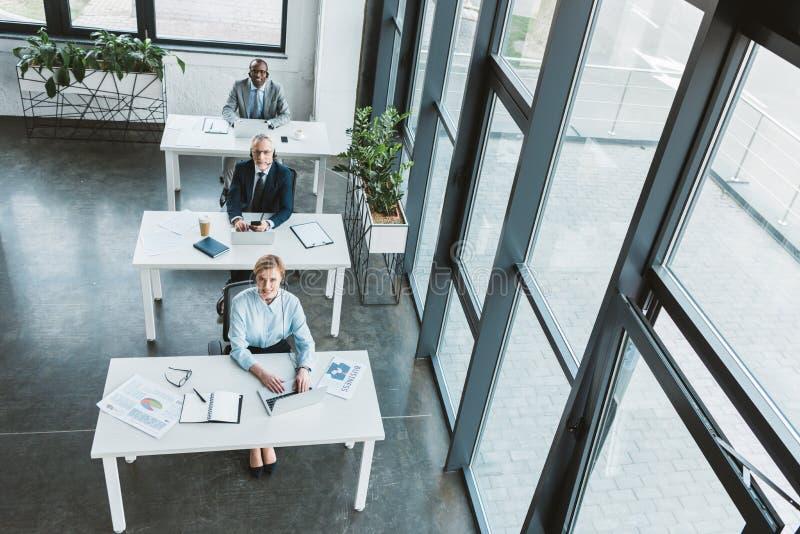 sikt för hög vinkel av multietniskt affärsfolk som sitter på tabeller och ser kameran royaltyfri fotografi