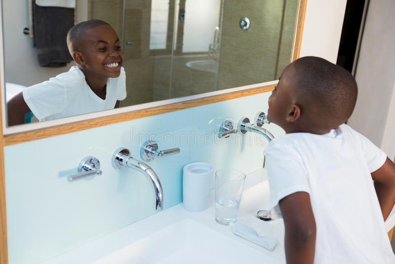 Sikt för hög vinkel av pojken som griper hårt om tänder, medan se spegeln arkivfoton