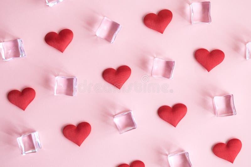 Sikt för hög vinkel av röda hjärtor och iskuber som är abstrakta mot pastellfärgad rosa bakgrund arkivbild