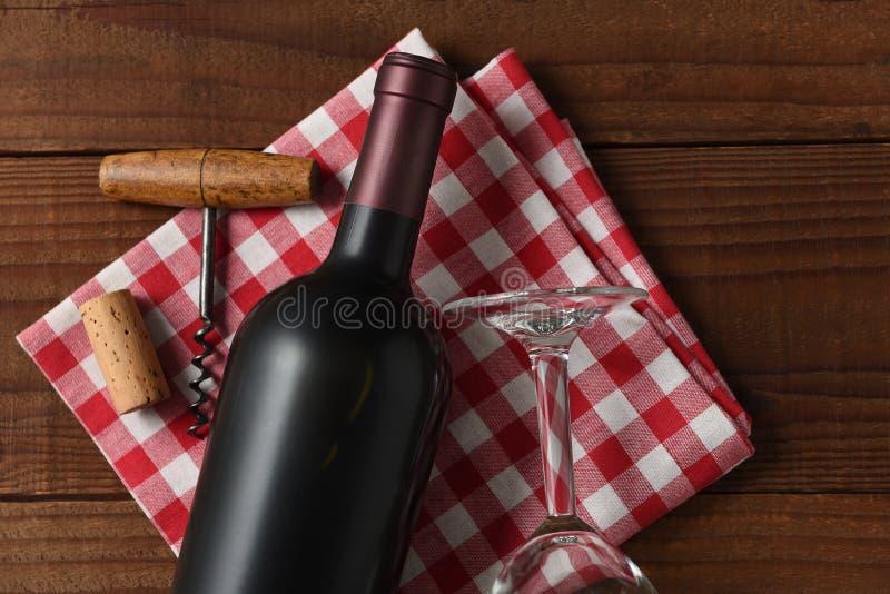 Sikt för hög vinkel för Closeup av en rött vinflaska på en röd och vit rutig servett royaltyfria bilder