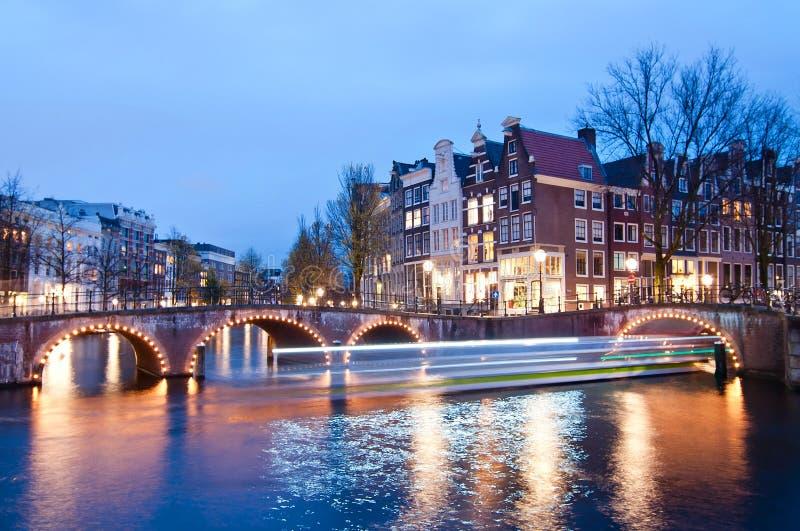 Sikt för Keizersgracht genomskärningsbro av den Amsterdam kanalen och historiska hus under skymningtid, Netherland royaltyfria foton