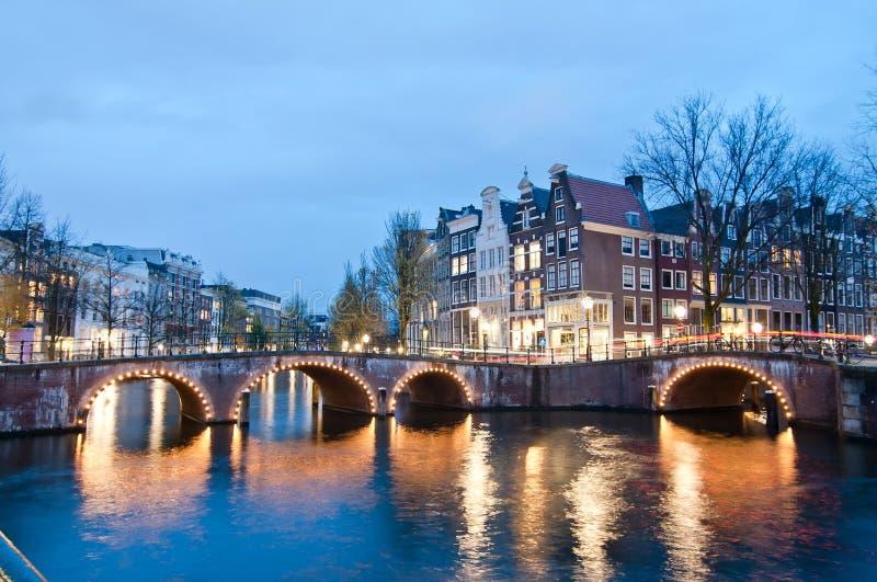 Sikt för Keizersgracht inersectionbro av den Amsterdam kanalen och historiska hus under skymningtid, Netherland royaltyfri bild
