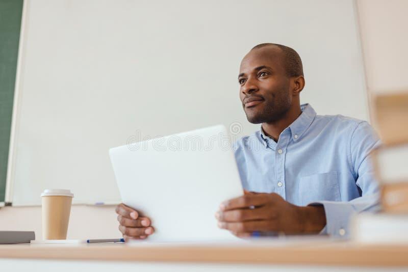 Sikt för låg vinkel av afrikansk amerikanläraresammanträde på skrivbordet med bärbara datorn och kaffe royaltyfri fotografi