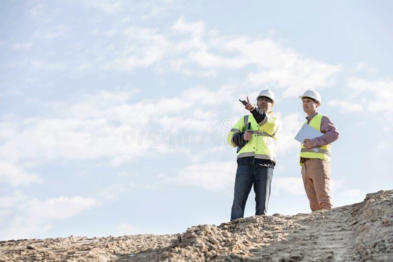 Sikt för låg vinkel av arbetsledare som diskuterar på konstruktionsplatsen mot himmel royaltyfri fotografi