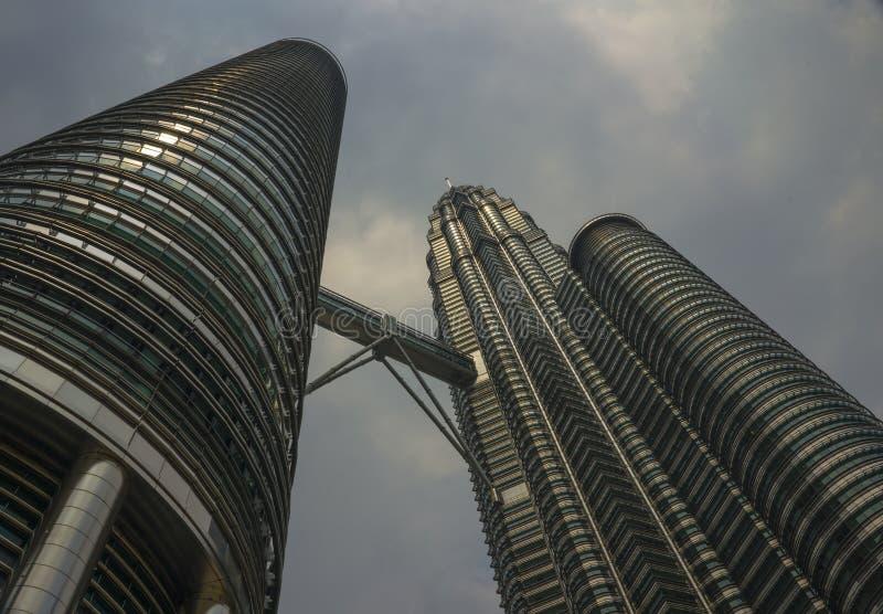 Sikt för låg vinkel av de bedöva Petronas tornen som reflekterar solen i metallfasaden som isoleras på en blå himmel i Malaysia royaltyfri foto