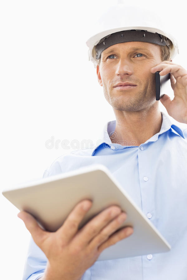 Sikt för låg vinkel av den manliga arkitekten med den digitala minnestavlan genom att använda mobiltelefonen mot himmel fotografering för bildbyråer