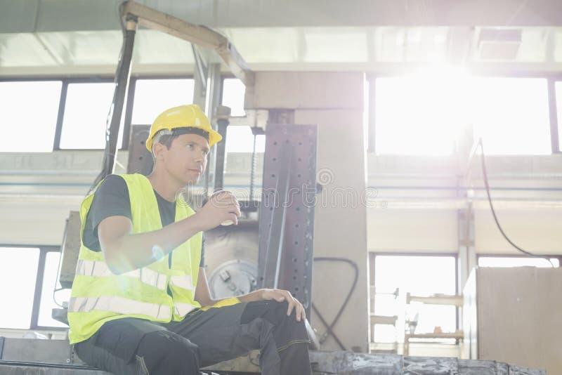 Download Sikt För Låg Vinkel Av Den Mitt- Vuxna Manuella Arbetaren Som Har Kaffe I Metallbransch Fotografering för Bildbyråer - Bild av sakkunskap, drink: 78727955