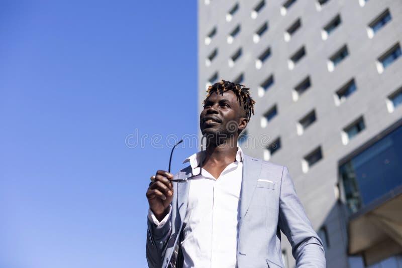 Sikt för låg vinkel av den svarta afrikanska unga mannen som bär elegant kläder med solglasögon som sätts in på glasögon, medan g royaltyfri foto