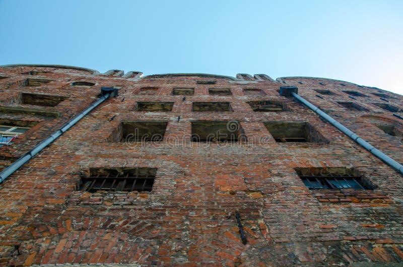 Sikt för låg vinkel av det övergav tegelstenhuset med brutna Windows med royaltyfria bilder