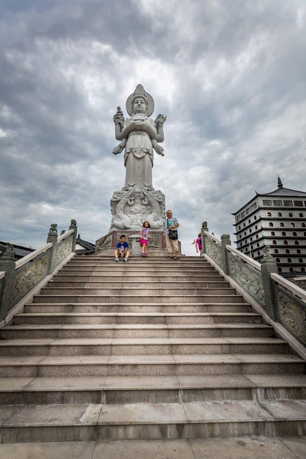 Sikt för låg vinkel av en familj på Dragon Gate på stenmoment bredvid en stor kinesisk staty med dramatisk himmel arkivfoto
