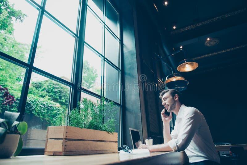Sikt för låg vinkel av en lyckad ung man och att ha en affärsconv arkivbild