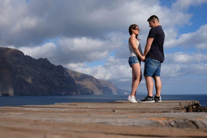 Sikt för låg vinkel av ett ungt par som rymmer händer med klippor, molnig himmel och havet i bakgrunden royaltyfri fotografi