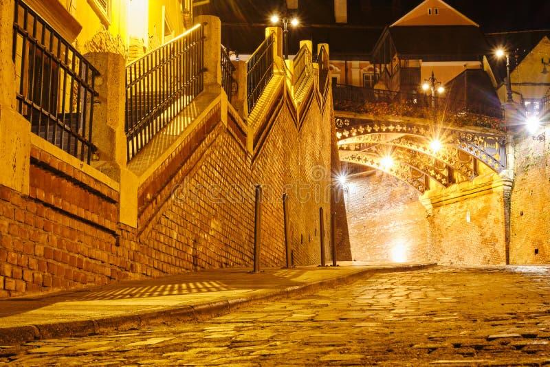Sikt för låg vinkel av lögnarebron Podul Minciunilor och bilpassagen in mot liten fyrkant i Sibiu, Rumänien, på natten arkivfoton