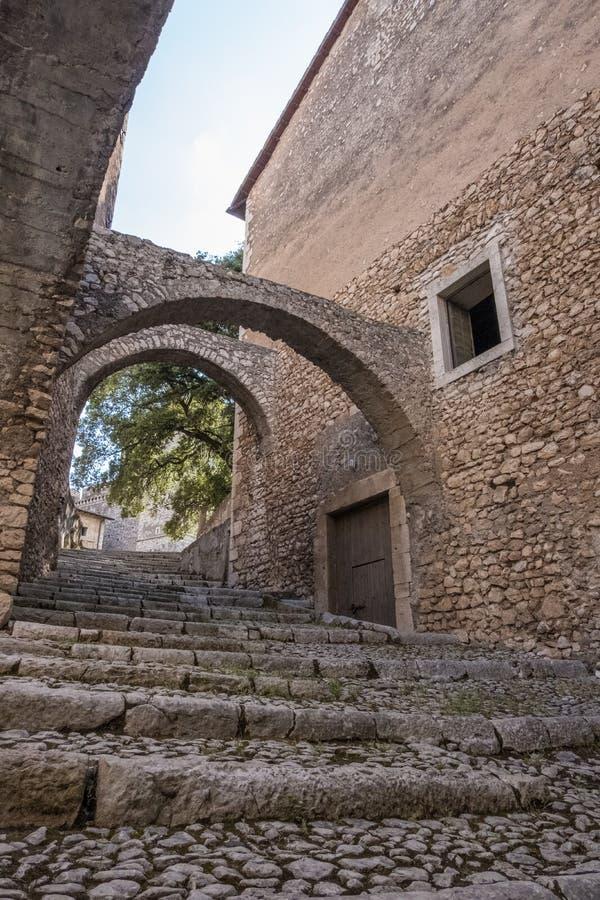 Sikt för låg vinkel av trappa och bågar av den medeltida slotten med vit himmelbakgrund arkivbild